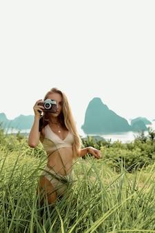 Fotógrafa caucasiana em lingerie bege sensual fazendo uma sessão de fotos com uma câmera vintage