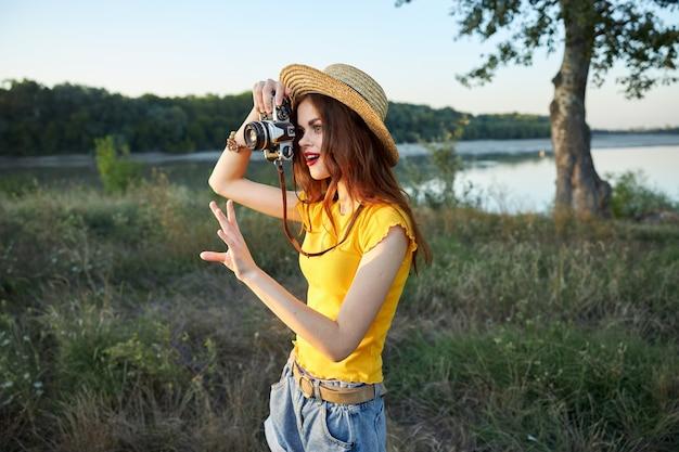 Fotógrafa com câmera e chapéu com lábios vermelhos caminhar ao ar livre