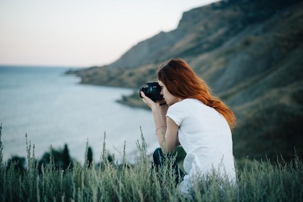 Fotógrafa com câmera nas montanhas