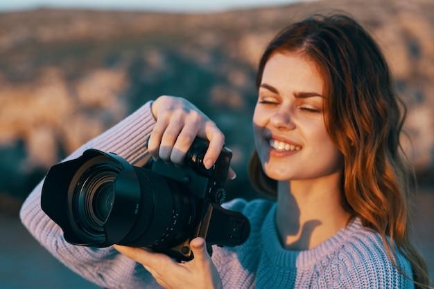 Fotógrafa de mulher feliz com câmera nas montanhas na natureza e no rio