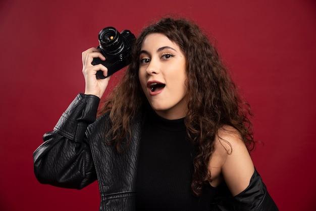 Fotógrafa de mulher vestida de preto, segurando uma câmera.