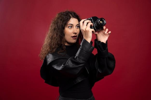 Fotógrafa de mulher vestida de preto, tirando fotos com uma câmera.