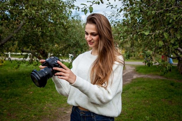 Fotógrafa de suéter branco e jeans tira uma foto com uma câmera profissional no parque