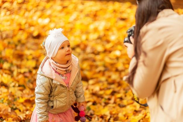 Fotógrafa e mãe tirando fotos da filha no parque de outono com folhagem amarela