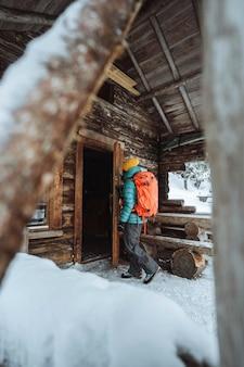 Fotógrafa entrando em uma cabana na floresta com neve