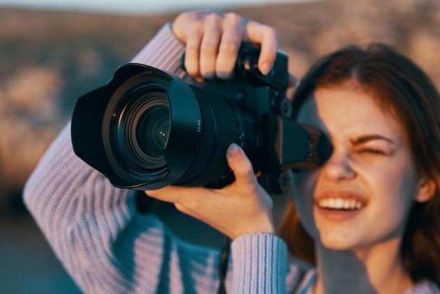 Fotógrafa feliz com câmera profissional flash para foto