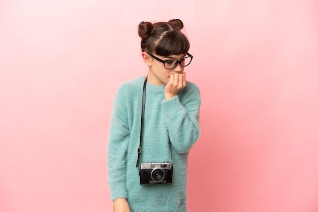 Fotógrafa isolada em um fundo rosa com dúvidas