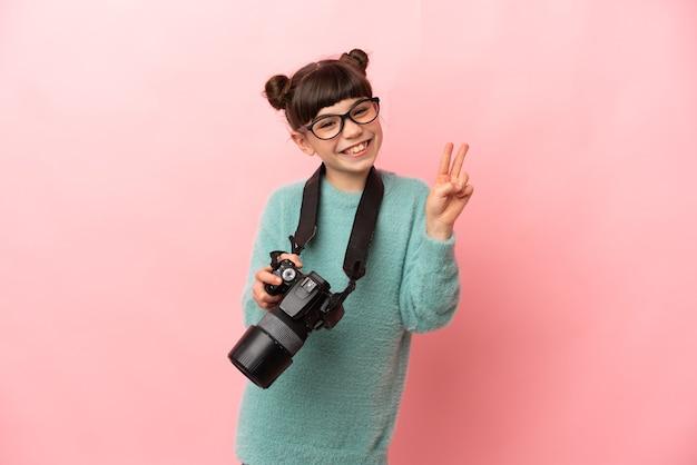 Fotógrafa isolada na parede rosa sorrindo e mostrando o sinal da vitória