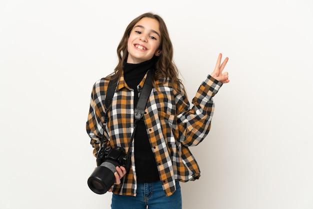 Fotógrafa isolada na parede sorrindo e mostrando o sinal da vitória