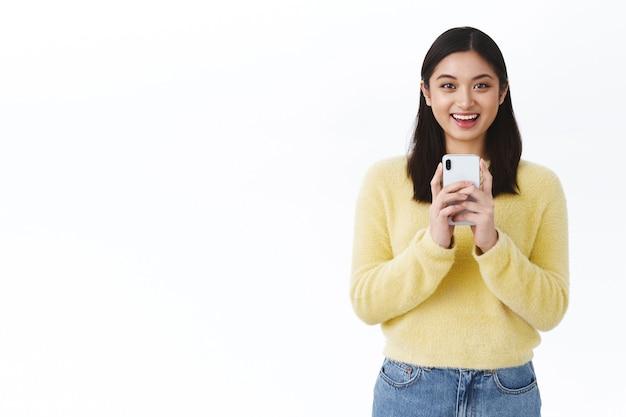Fotógrafa linda garota asiática tirando foto de um amigo no celular, sorrindo feliz, gravar vídeo usando smartphone, parede branca em pé com fluxo de blogger online