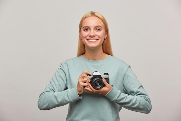 Fotógrafa loira emocional, parece inspirado e encantado, segurando na frente uma câmera fotográfica vintage retrô nas mãos