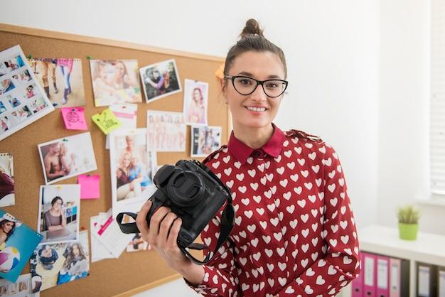 Fotógrafa profissional posando com sua câmera