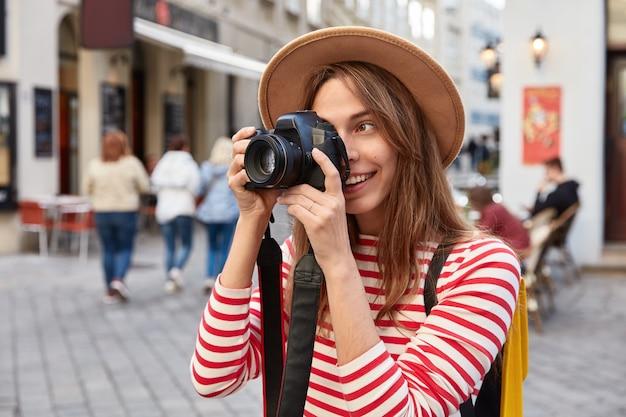 Fotógrafa profissional usa fotocâmera para fazer fotos, tira fotos de belas paisagens