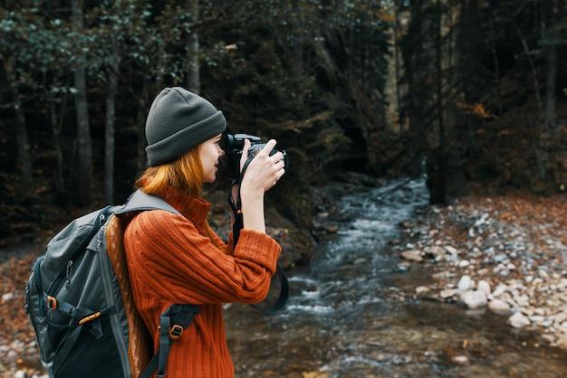 Fotógrafa segurando uma câmera na mão perto do rio nas montanhas e na floresta no