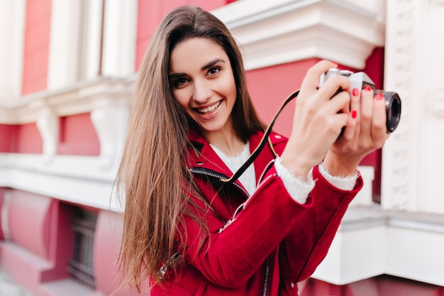 Fotógrafa sonhadora com manicure moderna trabalhando ao ar livre e rindo