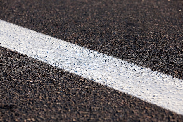 Fotografado em close-up da nova estrada para o movimento de veículos, uma cobertura escura das marcações da estrada da faixa de rodagem - listras brancas