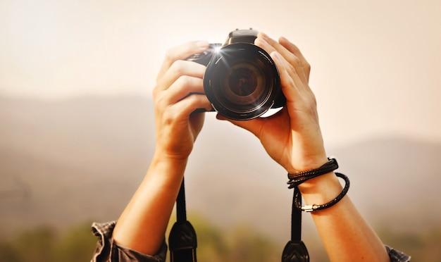 Fotografando a paisagem, close-up de um jovem fotógrafo asiático segurando a câmera