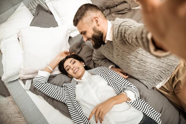 Fotografando a si mesmo. mulher atraente de cabelos escuros relaxando na cama enquanto o marido tirava fotos em uma loja de móveis