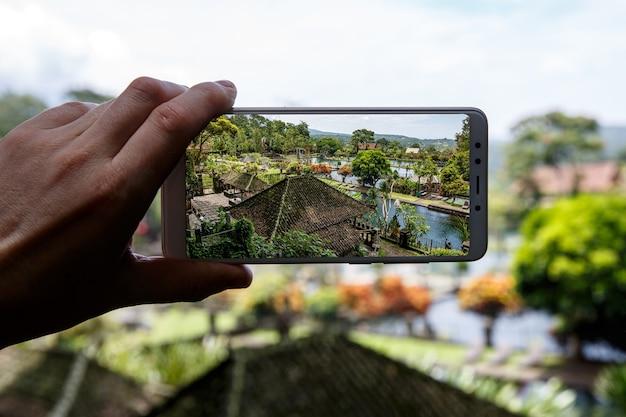 Fotografando com o smartphone na mão. conceito de viagens. palácio da água de tirta gangga em bali.
