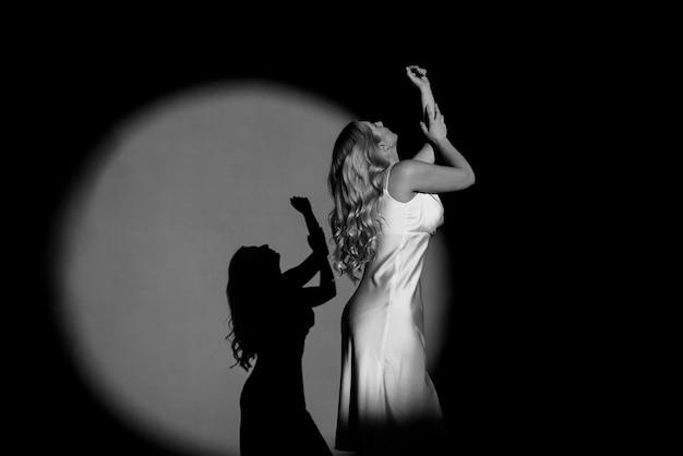 Fotografando com projetores, preto e branco, claro e escuro, com a figura de uma linda garota posando, tonificação na moda.