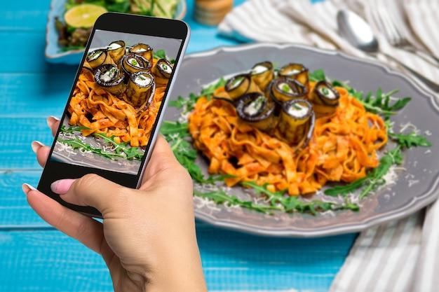 Fotografando comida conceito mulher tira foto de macarrão com berinjela, tomate, queijo, rúcula e salada