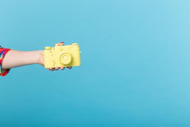 Fotografando e conceito vintage - mão feminina com câmera retro amarela na parede azul com espaço de cópia