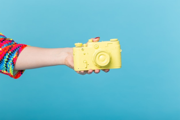Fotografando e conceito vintage - mão feminina com câmera retro amarela