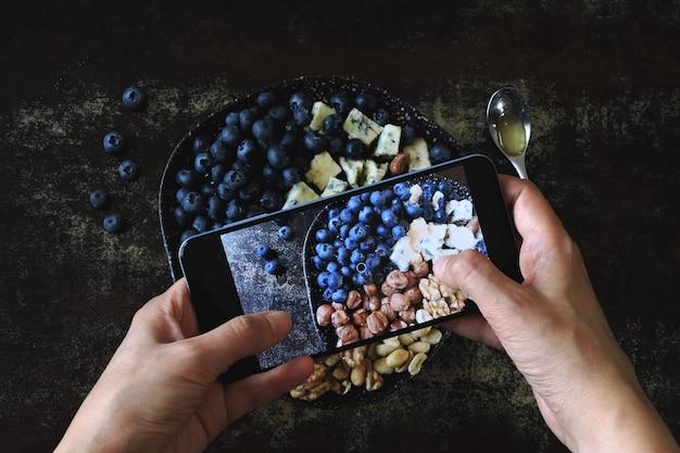 Fotografando uma refeição saudável em um telefone móvel. prato de queijo com mirtilos e nozes.