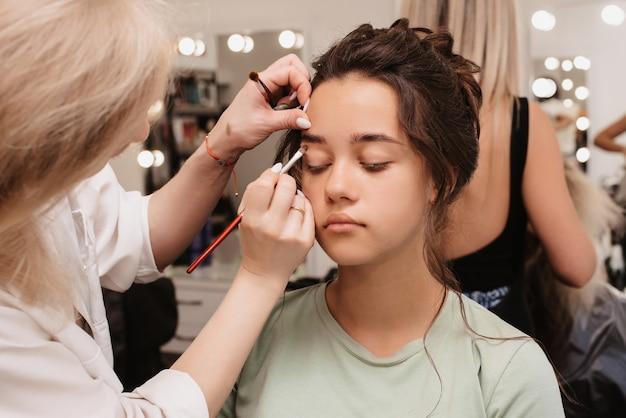 Fotografar em um salão de beleza. o maquiador aplica sombra nos olhos com um pincel macio.