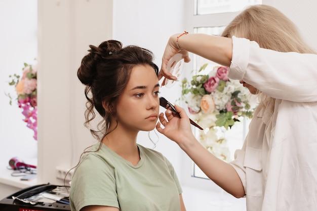 Fotografar em um salão de beleza. o mestre maquiador sombreia a base com um pincel.
