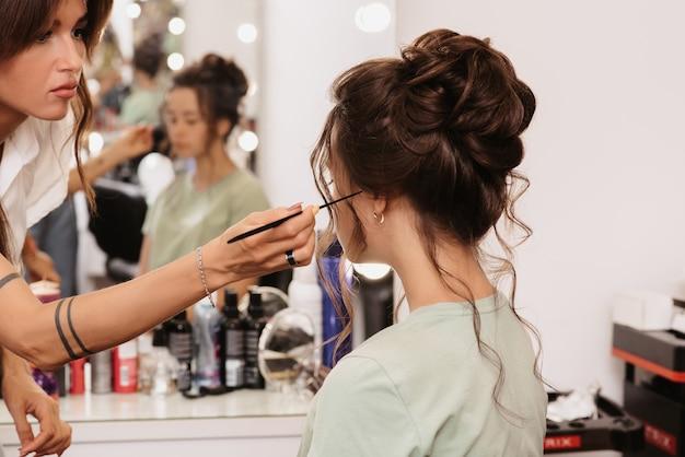 Fotografar em um salão de beleza. um cabeleireiro corrige o penteado de uma jovem morena com um pente.