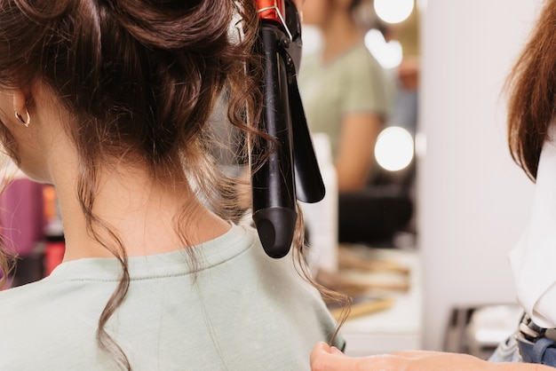 Fotografar em um salão de beleza. um cabeleireiro faz um penteado para uma jovem de cabelos escuros com um modelador de cabelo.