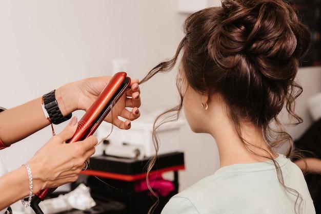 Fotografar em um salão de beleza. um cabeleireiro faz um penteado para uma jovem morena com a ajuda de um cabeleireiro.