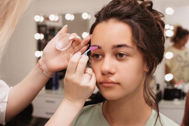 Fotografar em um salão de beleza. um maquiador faz um estilo de sobrancelha para uma jovem garota de cabelos escuros.