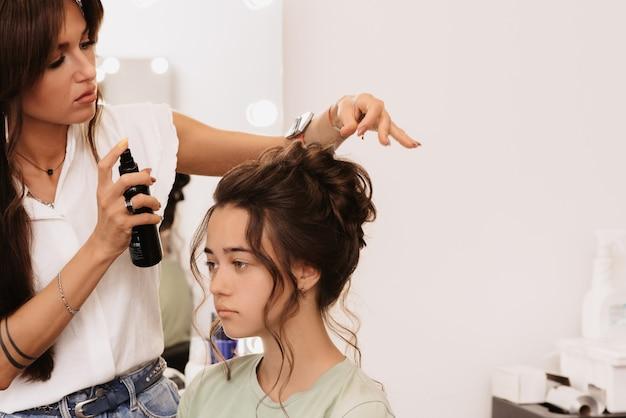 Fotografar em um salão de beleza. um mestre estilista faz o penteado de uma garota de cabelos escuros com a ajuda de fixá-lo com um spray de cabelo.