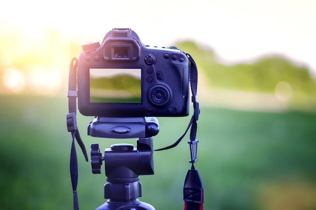 Fotografar uma câmera ao pôr do sol com um tripé no parque