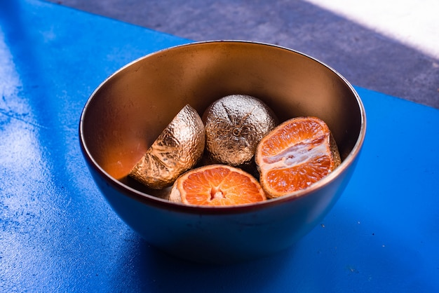 Fotografia abstrata de mandarinas banhadas em metal em uma tigela sobre uma superfície azul e madeira