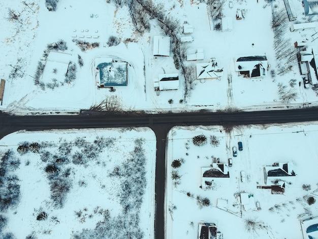 Fotografia aérea de casas, campos e árvores cobertas de neve durante o dia