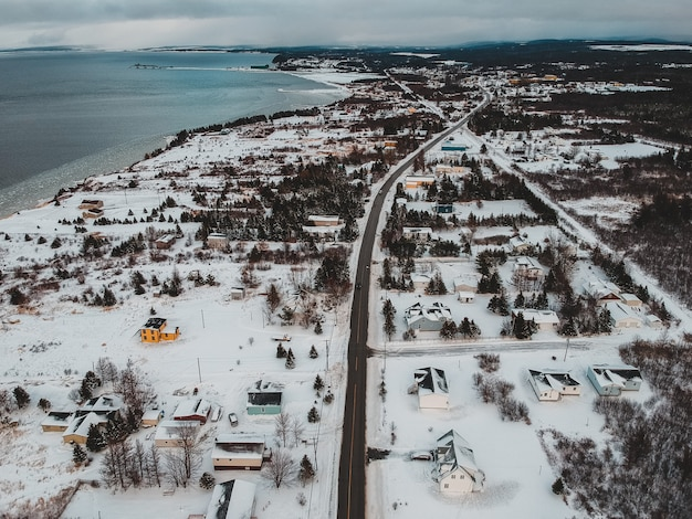 Fotografia aérea de casas no campo nevado, vendo o corpo de água sob o céu branco e azul