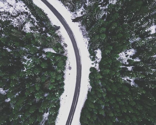 Fotografia aérea de drones de uma estrada no inverno, entre bosques com neve