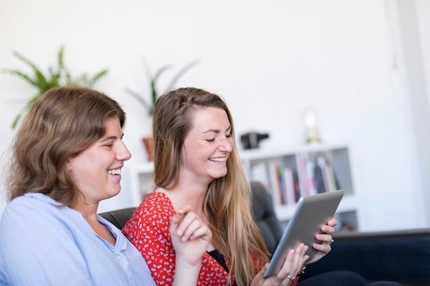 Fotografia aérea de duas mulheres bonitas em casa sentado no sofá ou sofá usando um computador tablet pc e sorrindo