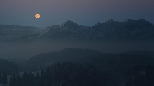 Fotografia aérea de uma montanha observando a lua cheia