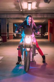 Fotografia com neons azuis e rosa em uma motocicleta. jovem modelo loira caucasiana posando com uma jaqueta de couro preta
