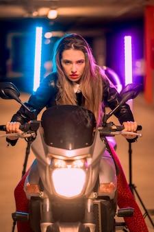 Fotografia com neons azuis e rosa em uma motocicleta. retrato de uma jovem loira e bonita, branca, com uma jaqueta de couro preta