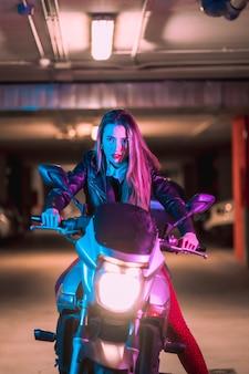 Fotografia com neons azuis e rosa em uma motocicleta. retrato de uma jovem modelo loira branca vestindo uma jaqueta de couro preta