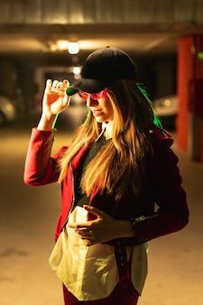Fotografia com neons vermelhos e verdes em um estacionamento. jovem loira e bonita, branca, de terno vermelho, óculos escuros e boné preto