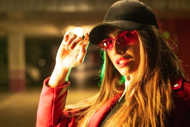 Fotografia com neons vermelhos e verdes em um estacionamento. retrato de uma jovem loira caucasiana de terno vermelho, óculos escuros e boné preto