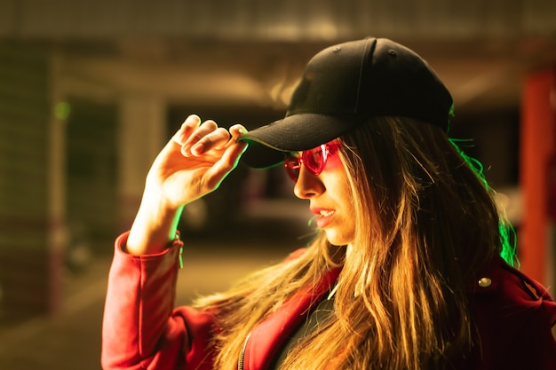 Fotografia com neons vermelhos e verdes em um estacionamento. retrato de uma jovem loira e bonita, branca, de terno vermelho, óculos escuros e boné preto