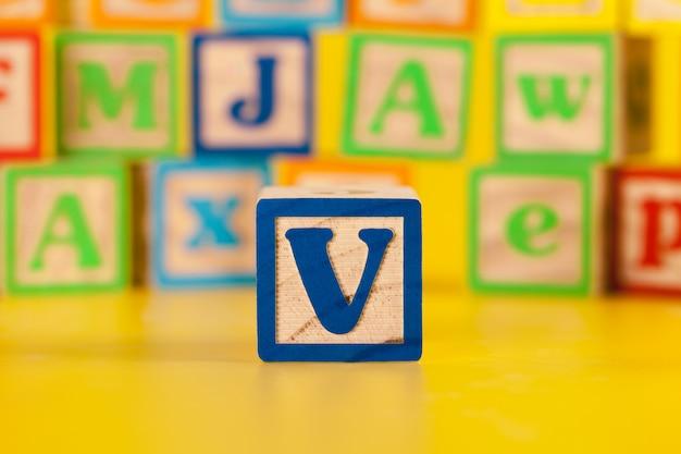 Fotografia da letra de madeira colorida do bloco v
