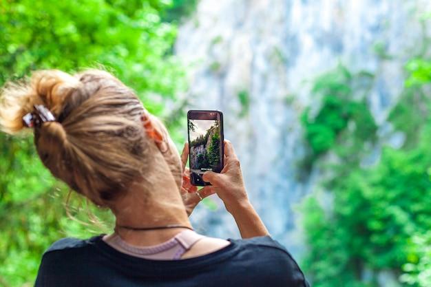 Fotografia da natureza com a ajuda de um smartphone por um jovem turista em viagem.